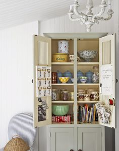 Use a vintage hutch for storage in your kitchen.  Paint one to match the kitchen, and then try a complementary color on the interior.  Customize it by adding even more organizing tools to the inside of the doors, such as a key rack, a message board, or even a basket to hold mail.  Arrange like items or any collections you may have together to create pleasing symmetry.    Apply shelf paper to ease routine cleaning, or use old wallpaper remnants instead.