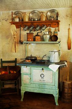 Old Stove...prim coffee grinders & pewter plates & mugs above the stove.