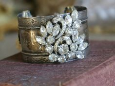 Mercy bracelet~ An old silver plated napkin ring is recycled into a cuff bracelet. A rhinestone brooch is the centerpiece. Around the back are vintage escutcheons tied with a bit of antique lace. crownedbygrace.
