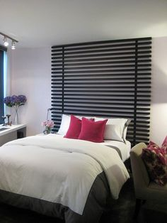 Painted wood slats, with some simple assembly, become a dramatic headboard when taken up to the ceiling.
