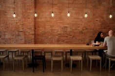 dining table with stools beer tasting, bricks, exposed brick, wooden tables, wall lighting, long tables, dining tables, wall design, salt
