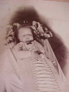 little child in elaborate burial dress