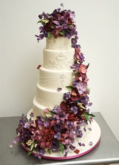 Nice PinSix stacked round tiers are covered in ivory fondant and adorned with a spiral cascade of sugar flowers in hues of purples and mauves. Included are calla lilies, cymbidium orchids, vanda orchids, tulips, blackberries, lisianthuses, peony leaves, sweet peas, roses, dendrobium orchids, and hydrangeas. Cake design by Ron Ben-Israel. purple-weddings Super job