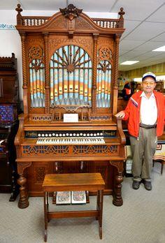 Dick Rhea with his prized pump organ at Rhea's Antique Pump Organs in Sharon Springs, Kansas.