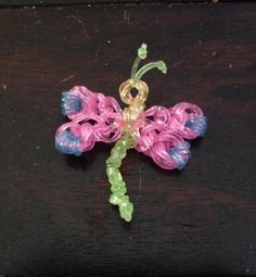 Dragonfly charm made by Linda Kolasa. Inspired by Made by Mommy's snowflake charm. To make the head wrap a band around the hook 3 times and slide it on another band and slip knot it. (Wings are 1 band looped 4 times on hook slid onto 2 bands and add 2 single looped bands to it.) (Make 4 wings) Take head use slip knot band  slide the wings on secure it with wrapping band around head. Body is just  5 cap bands looped together with knots tied in them secure in center of body and loop over head.