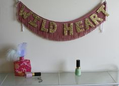 Fabric fringe (bought by the yard) with hand glittered letters.  The description mentions rectangular glitter.