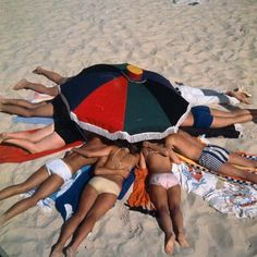 Sunbathers in circle with heads under low umbrella at Bondi, 1966. National Archives of Australia.