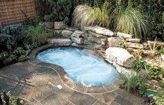 A little 'oasis' was created in this compact urban yard as a 'mini pool' for a family with young children. The plunge-pool/spa with black slate interior and integrated rock feature, has a waterfall surrounded by the lush plantings. The deck is natural square-cut flagstone set on a concrete base. A natural cedar hedge and custom cedar side screens provide privacy. With equipment in the garage, insulated plumbing lines and a custom cover allow for year round use. (8 x 13, kidney shape)