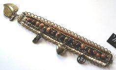 Pulseira em níquel ouro envelhecido com 1 fio cental  de sementes de acaí e pingentes, 4 fios de miçangas e 2 fios de corrente. Fecho lagosta com pingente coração. R$ 29,00
