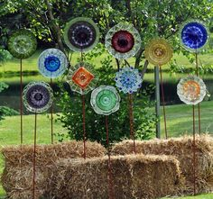 Recycled Glass Flower Sun Catcher Garden Art. I'm not much about the hay, I'd like them stuck straight into the ground with foliage around :)