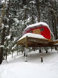 Red tree house in the snow.