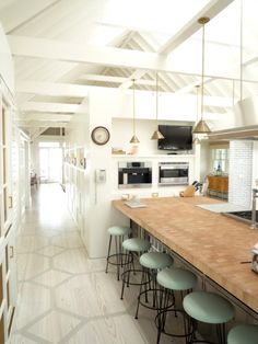 Great use of a long and narrow space for a kitchen  and love the touch of color with the Minty green barstools.