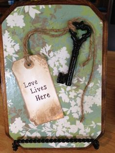 DIY - LOVE LIVES HERE wooden plaque  1.  Varnish or paint plaque. Hobby Lobby $2.99.  After dry add a coat of Modge Podge to surface and sides.  Background - Adhere a cut-to-size piece of scrapbook paper, press for smooth surface.  Cover surface with Modge Podge brushing on in a criss-cross fashion.   Tag - To give the aged appearance, dab edges with the same varnish or use a tea bag.  I used varnish.  Print a saying of your choice.  Attach a piece of twine to a key and Modge Podge in place.