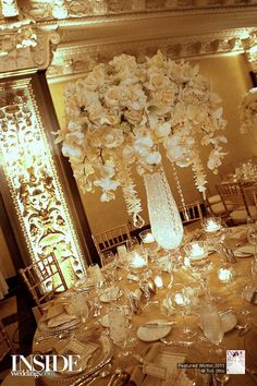 Large table centerpieces of white roses, hanging phalaenopsis ochids, strung dendrobium orchids with crystals at end. This is what I want, just some purple added in