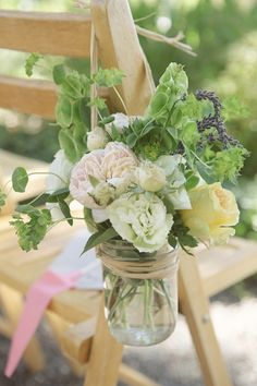 These mason jar bouquets are perfect to line your aisle with and then you can reuse them as centerpieces for your reception.  The soft creams and green colors would make a stunning arrangement!