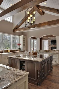 exposed beams, ceiling beams, high ceilings, vaulted ceilings, open kitchens, white cabinets, wood beams, dream kitchens, island