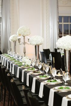Simple and elegant...black tablecloths, white flowers.