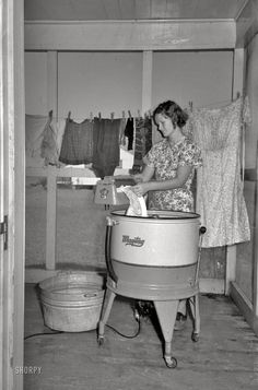 """Mrs. Maytag: September 1938. """"Farm wife washing clothes. Lake Dick Project, Arkansas."""" 35mm negative by Russell Lee, Farm Security Administration. Click to view full size."""