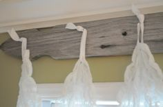 Curtains hung from hooks on an old fence post