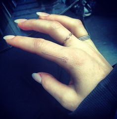 Ellie Goulding's white tattoo. I'm really digging tiny images in white. It just seems so dainty. arrow tattoo, tattoo ideas, ring finger, white tattoos, elli gould, finger tattoos, white ink tattoos, cross, ellie goulding