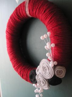 Just get a foam wreath, wrap it in yarn and add some homemade felt roses :) simple