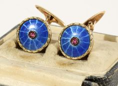 A PAIR OF FABERGE GOLD AND GUILLOCHE ENAMEL CUFFLINKS, 1908-1917   a laurel wreath border envelopes translucent blue enamel over a wavy sunburst guilloche ground, a ruby cabochon decorates the center, 2.5 cm. (1 in.) overall, maker's mark of Faberge