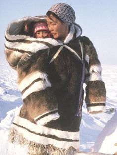 Inuit woman carries baby in her amauti, a babywearing coat. Made of caribou skin the baby sits in a pouch up against the mother's back. The hood pulls over them both for warmth and protection from snow.