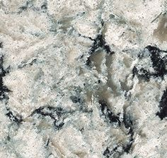Praa Sands from Cambria's Waterstone Collection. The subtle yet striking veining in Praa Sands mimics the rock outcroppings that dot this breathtaking stretch of beach on England's southernmost coast. Neutral clouds of gray and cream add balance and richness, while random hits of ocean blue and mirrored flecks mimic the glistening sea. #Cambria #CambriaQuartz #Quartz