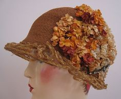 """Art Deco, 1920s cloche hat. It is so elegant!  This hat is made of fine, tightly woven rows of silk braid in a deep peach color. The hat has a crown of pink and peach colored flowers caught with a large rhinestone, jewel set, metal ornament. There are silk fuzzy flower centers in the largest of the flowers near the jewels. The embroidered silk label reads: """"Established 1880 Classic 14 Inc. San Francisco"""".   Brim is raffia over a wire grid."""