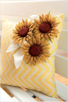Clip the stems from our   cuter-than-the-real-thing sunflowers. Then cluster them   on a frame, a basket—or a sunny, striped pillow.   (Chevron pillow cover: Sold in the Fabric Department.)