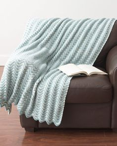 An elegant ripple pattern crocheted in dreamy blue and cream shades makes this blanket a cozy and calming addition to any room. Shown in Bernat Denimstyle.