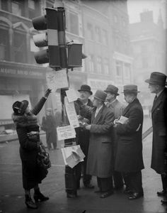 U.K. A group of people checking the addresses attached to a traffic light, a novel 'change of address bureaux' for many bombed out businesses in the City of London during the blitz, January, 1941 // Photo by Keystone/Getty Images)