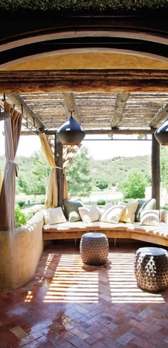 Will and Jada Pinkett Smith's California bedroom terrace, decorated by Judith Lance, has pendant lights by Tom Dixon, drum tables by Studio JRM, and cushions covered in Donghia, Holly Hunt, and Perennials fabrics.