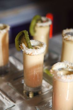 How chic are these shot glasses rimmed with fresh coconut and a kiwi garnish?