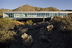 A glass house in the Arizona desert that bridges a dry river.