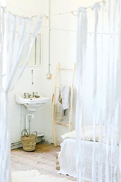 An all-white bedroom with sheer curtains and a white porcelain sink.
