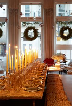 For Rose's Christmas party, the designer ingeniusly uses empty wine bottles to hold varying heights of white candles up and down a formally set table.