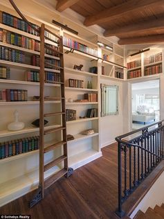 Tyra Banks's Beverly Hills Mansion: Up a flight of stairs accented with wrought iron, a rolling ladder runs the length of an impressive library.