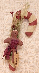 G1498 - Sweets Candy Cane   A stuffed gingerbread man and winter greenery accent  9 1/2