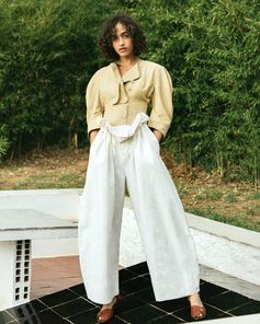 Corsetry detailed tailoring collides with wide leg, cinched waist trousers for a statement silhouette.