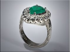 "14K white gold vintage style fashion ring with pear shaped emerald in center, surrounded by round diamonds set in a ""fishtail"" style setting. Designed and made by Ron Litolff of Gemstone Designs."
