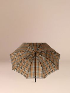 Sartorial walking umbrella handmade in the UK Canopy is lined in check fabric double woven in Italy and finished with sustainable non-PFC coating Maple wood handle crafted in Italy Press-stud tab closure