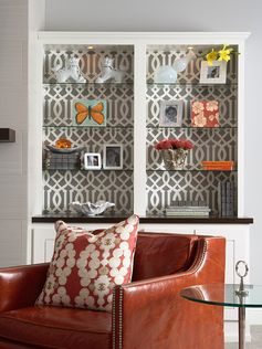 DIY bookcase decor. Wallpaper / contact paper / fabric covering cardboard pieces cut to size to fit snugly on the back wall of your bookcase. Now you can change it out with the seasons without damaging your bookcase.