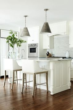 A sunny, bright kitchen. The all-white cabinets and light marble enhance the light. The gray lampshades add a bit of contrast.