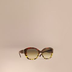 Italian-made sunglasses in tortoiseshell acetate. The oversize square frame features an ombré in amber yellow and cardinal red. In tribute to our trench coat, a three-dimensional buckle detail accents the grey tortoiseshell temples, and gradient green scratch-resistant lenses offer 100% UV protection.