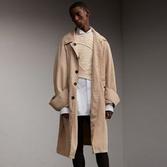A unisex car coat crafted in England from new lightweight tropical gabardine, with exaggerated details. The tonic-coloured cotton twill is woven for weatherproof protection at the Burberry mill, and tumbled and washed to imbue softness and fluidity. Complementing the supple drape of the cloth, it is cut for a relaxed fit with minimal lining.