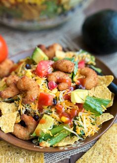 This easy Layered Popcorn Shrimp Taco Salad recipe is perfect for an easy, breezy summer time meal! Layers and layers of flavor make this a meal the whole family will love!   MomOnTimeout.com   #dinner #salad #ad