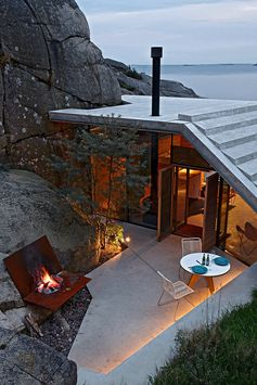 A tiny seaside house with outdoor fireplace and concrete roof.