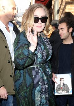 Adele greets fans while out in NYC.