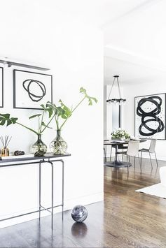 A gray console table against white walls with charcoal drawings. There is also a metal reed diffuser and banana leaves and a dining room beyond.